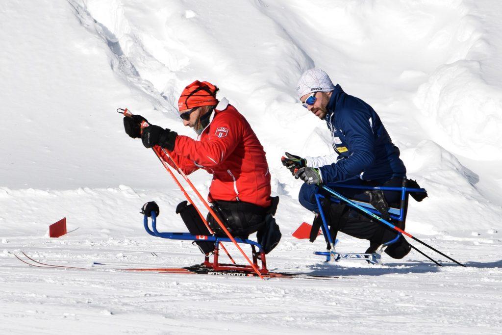 2 personnes faisant du paraski de fond en luge adaptée